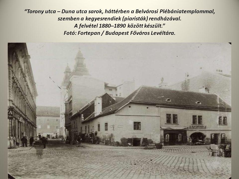 """""""Torony utca – Duna utca sarok, háttérben a Belvárosi Plébániatemplommal, szemben a kegyesrendiek (piaristák) rendházával. A felvétel 1880–1890 között"""