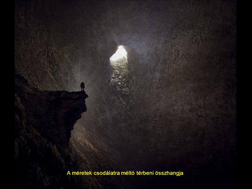 Egy hatalmas fénysugár, vízesés formájában sugározza be a barlangot, a hatalmas stalagmit oszlop mellet eltörpülve, egy barlangász.