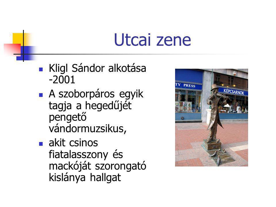Utcai zene  Kligl Sándor alkotása -2001  A szoborpáros egyik tagja a hegedűjét pengető vándormuzsikus,  akit csinos fiatalasszony és mackóját szoro