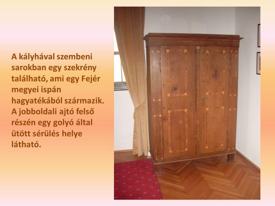 A kályhával szembeni sarokban egy szekrény található, ami egy Fejér megyei ispán hagyatékából származik. A jobboldali ajtó felső részén egy golyó álta