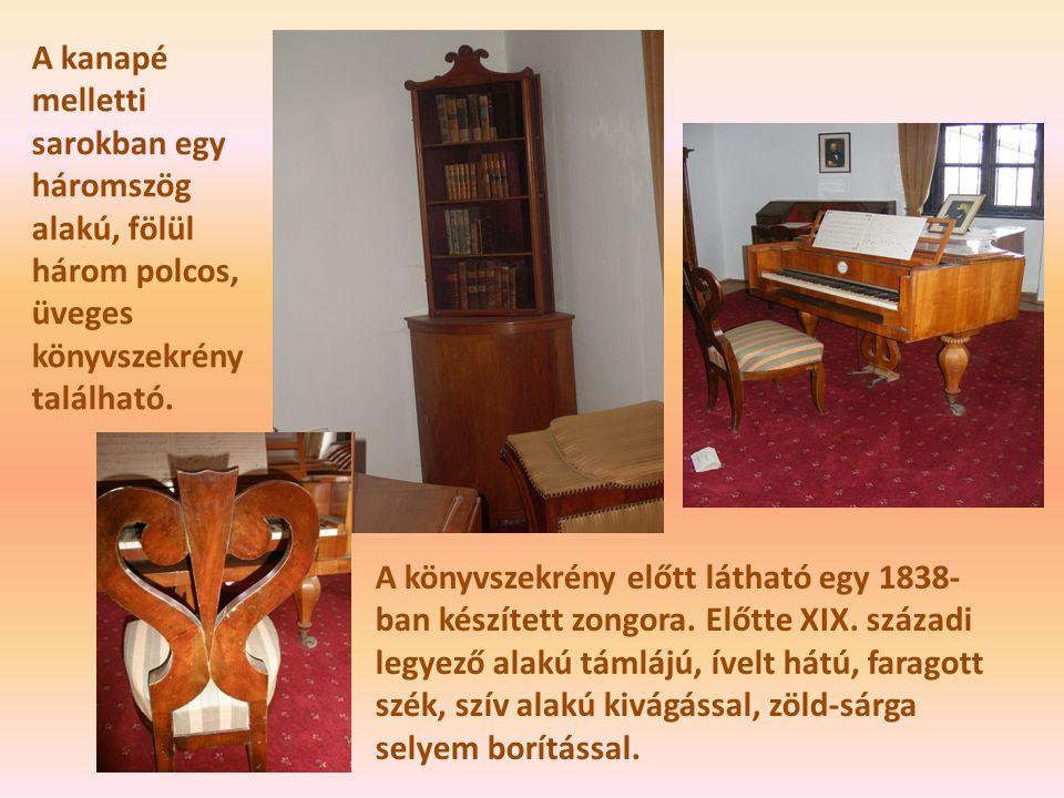 A kanapé melletti sarokban egy háromszög alakú, fölül három polcos, üveges könyvszekrény található. A könyvszekrény előtt látható egy 1838- ban készít
