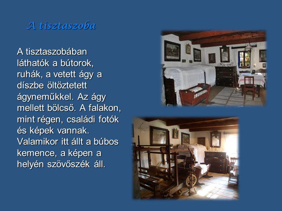 A tisztaszoba A tisztaszobában láthatók a bútorok, ruhák, a vetett ágy a díszbe öltöztetett ágyneműkkel. Az ágy mellett bölcső. A falakon, mint régen,