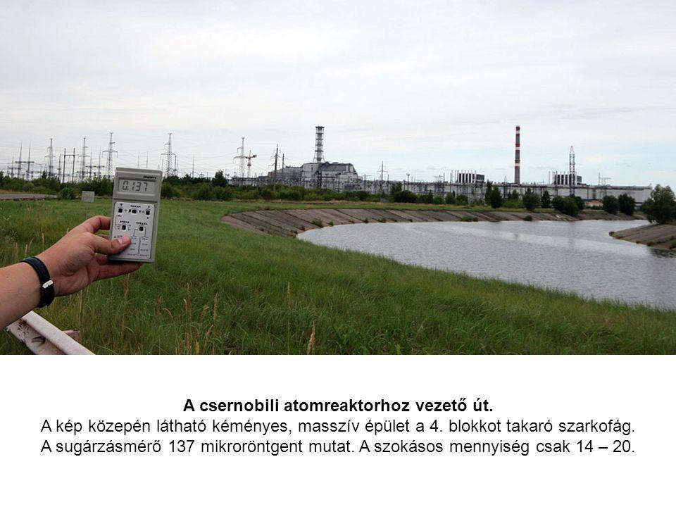 A csernobili atomreaktorhoz vezető út. A kép közepén látható kéményes, masszív épület a 4. blokkot takaró szarkofág. A sugárzásmérő 137 mikroröntgent