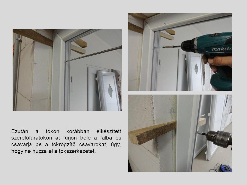 Ezután a tokon korábban elkészített szerelőfuratokon át fúrjon bele a falba és csavarja be a tokrögzítő csavarokat, úgy, hogy ne húzza el a tokszerkez