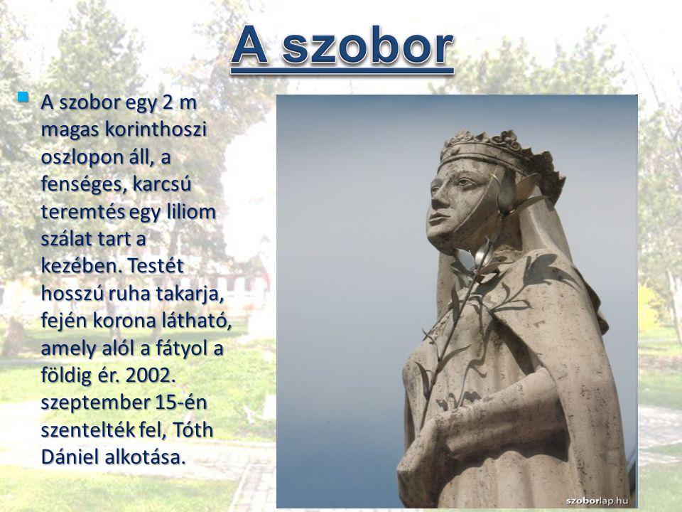  A szobor egy 2 m magas korinthoszi oszlopon áll, a fenséges, karcsú teremtés egy liliom szálat tart a kezében. Testét hosszú ruha takarja, fején kor