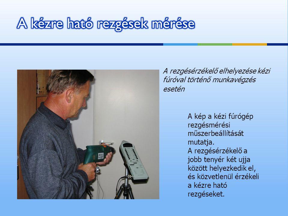A kép a kézi fúrógép rezgésmérési műszerbeállítását mutatja. A rezgésérzékelő a jobb tenyér két ujja között helyezkedik el, és közvetlenül érzékeli a