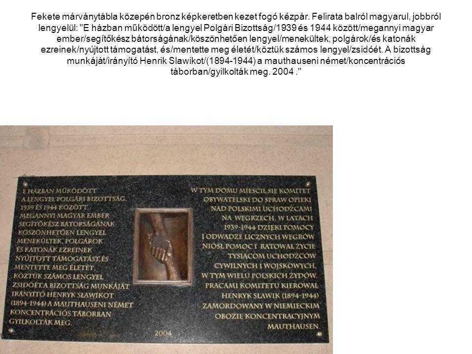 Fekete márványtábla közepén bronz képkeretben kezet fogó kézpár. Felirata balról magyarul, jobbról lengyelül: