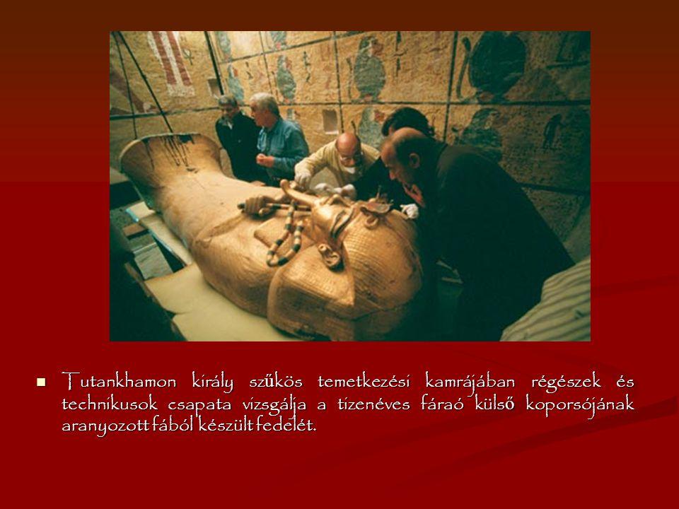 Tutankhamon király sz ű kös temetkezési kamrájában régészek és technikusok csapata vizsgálja a tizenéves fáraó küls ő koporsójának aranyozott fából ké