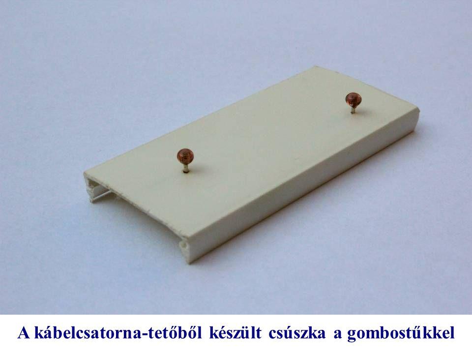 A kábelcsatorna-tetőből készült csúszka a gombostűkkel