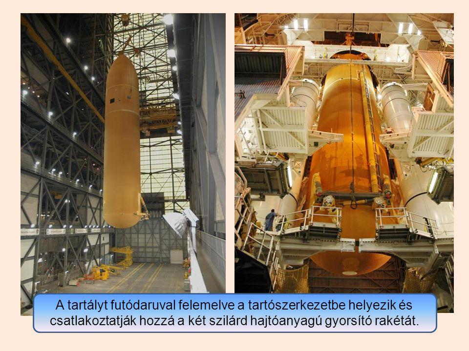 A tartályt futódaruval felemelve a tartószerkezetbe helyezik és csatlakoztatják hozzá a két szilárd hajtóanyagú gyorsító rakétát.