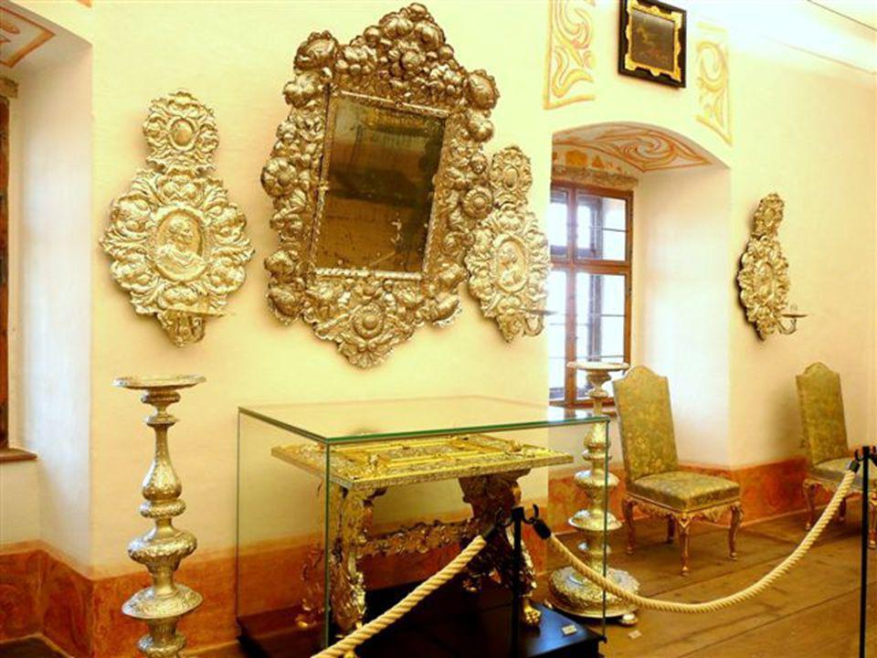 Ezüst tükör az aranyozott, ezüst asztal felett Ezüst falikarok és gyertyatartók