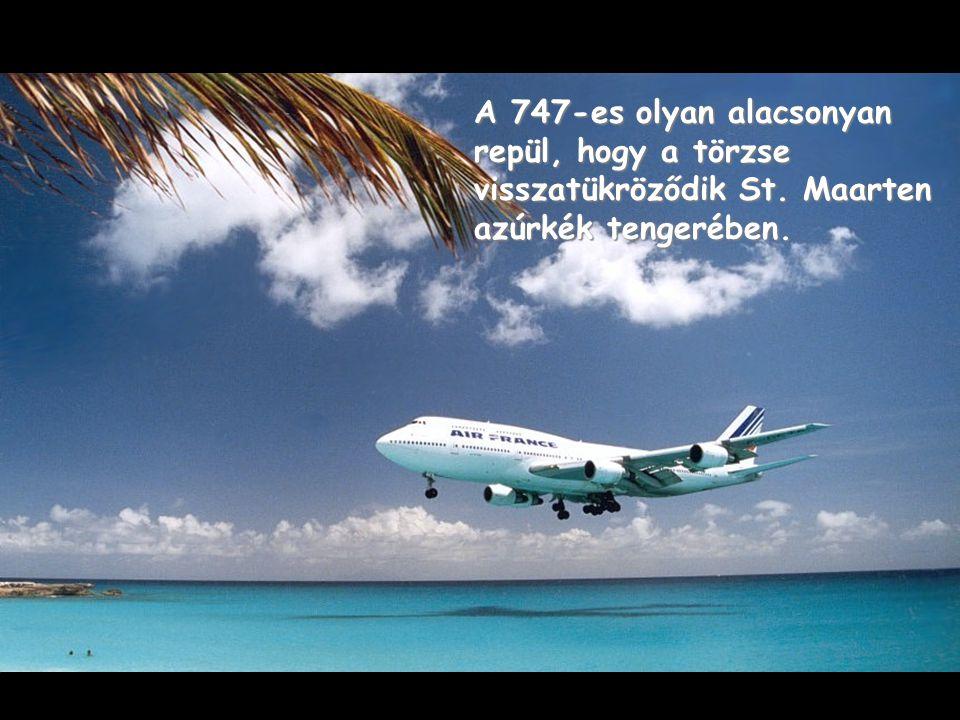 A 747-es olyan alacsonyan repül, hogy a törzse visszatükröződik St. Maarten azúrkék tengerében.
